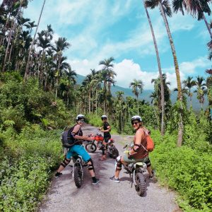 three foreign travellers are enjoying the time riding motocross on the Guangfu trail.