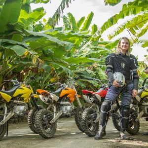 Two foreign gils are posting with banana grove and the motocross